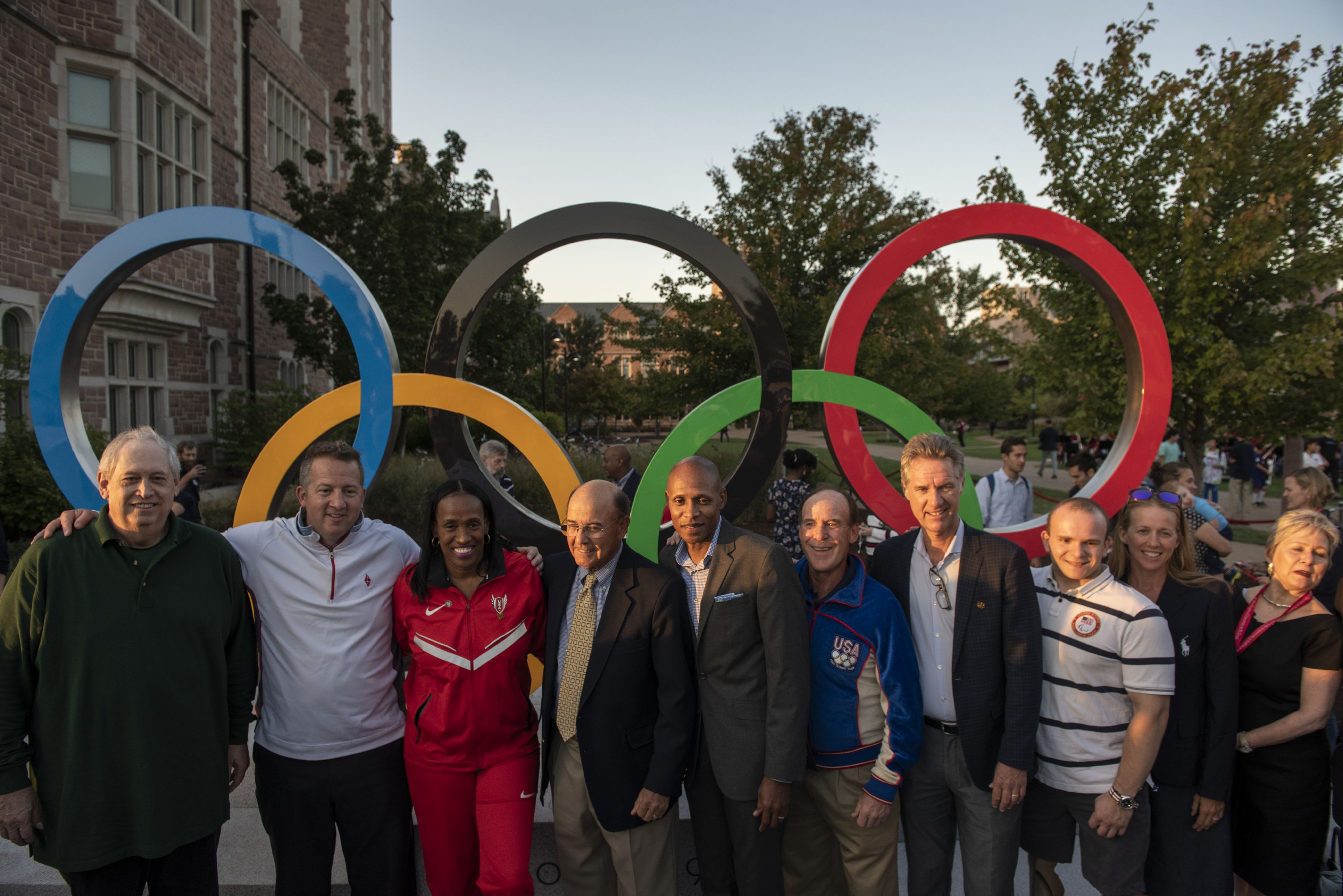 A group of people standing in front of the Olympic Rings sculpture