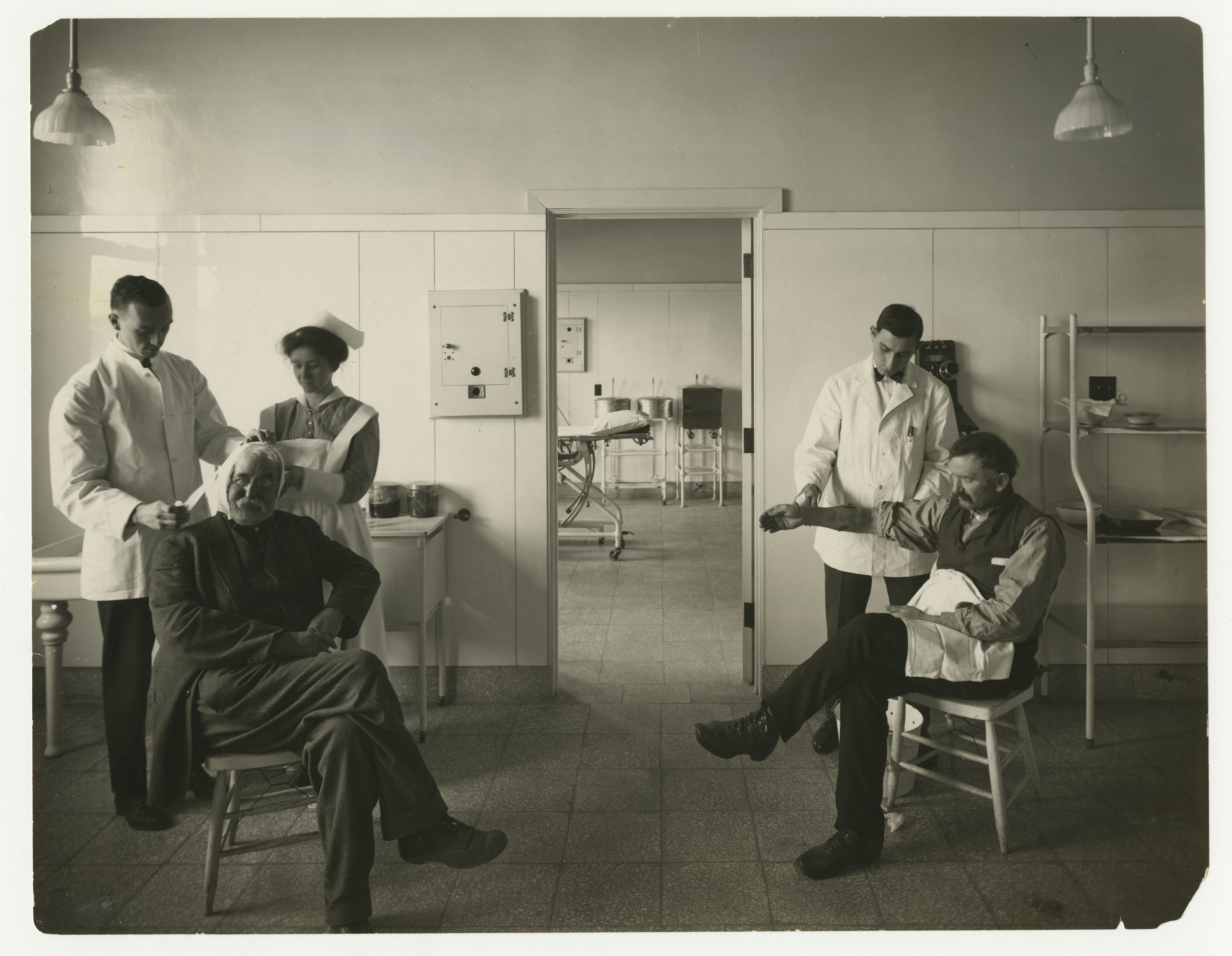 Black and white photo: Three caregivers treat two seated patients