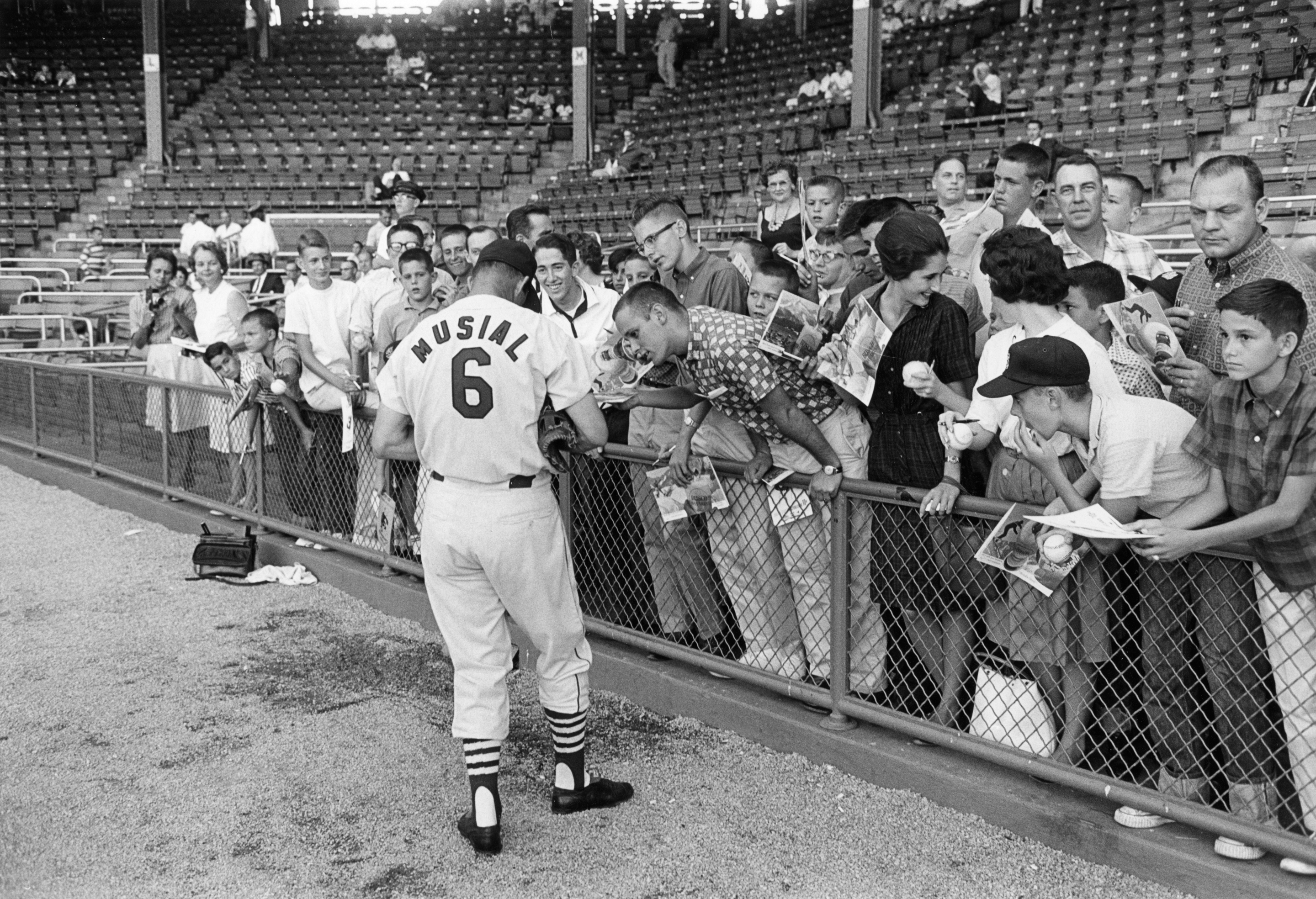 Black and white photo of Stan Musial signing autographs for crowd of spectators in a stadium